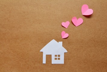 Paper cut of love family house on brown background, happy family concept.