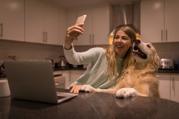 Girl taking selfie with her dog in kitchen