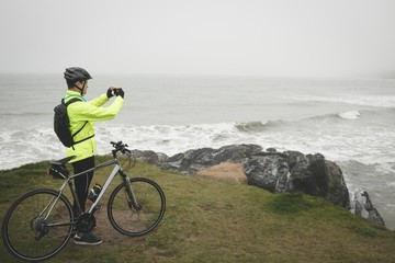 Man with cycle taking photo from mobile phone