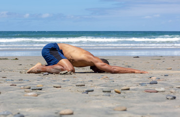 Athletic man at the beach doing yoga on the sand in Child's  Pose