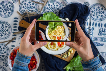 Woman hands make photography of food with phone. Cooked white corn grains, Smartphone photo of lunch for social media or blogging. Raw vegan vegetarian healthy food