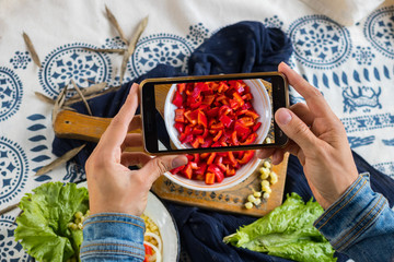 Woman hands make photography of food with phone. Red bell pepper salad. Smartphone photo of lunch for social media or blogging. Raw vegan vegetarian healthy food