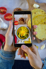 Woman hands make photography of food with phone. Corn soup with vegetables. Smartphone photo of lunch for social media or blogging. Raw vegan vegetarian healthy food
