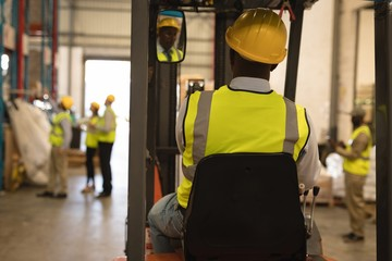 Male worker driving forklift