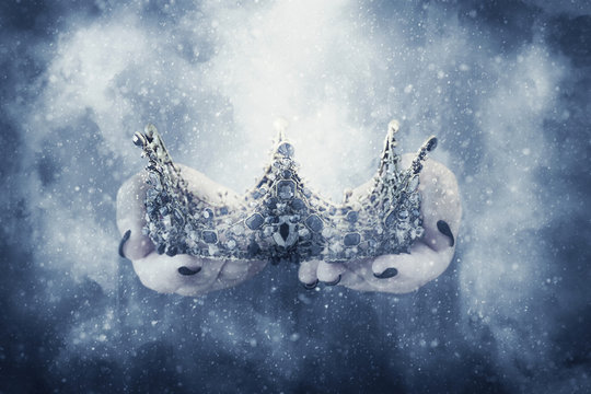 image of lady in black holding queen crown decorated with precious stones. fantasy medieval period. Black queen.
