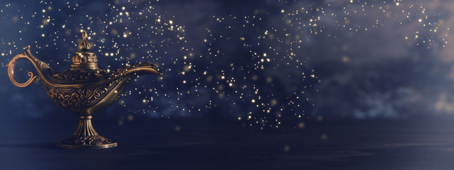 Image of magical mysterious aladdin lamp with glowing glitter lights over black background. Lamp of wishes.