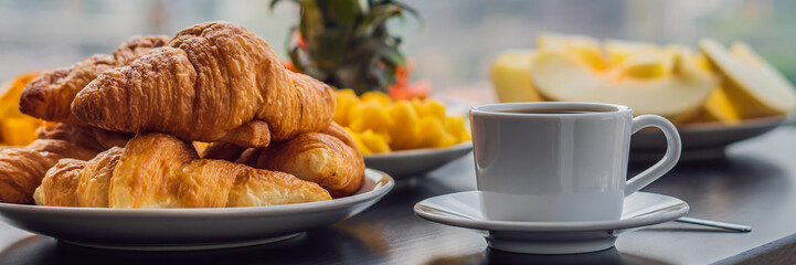 Breakfast table with coffee fruit and bread croisant on a balcony against the backdrop of the big city BANNER, long format