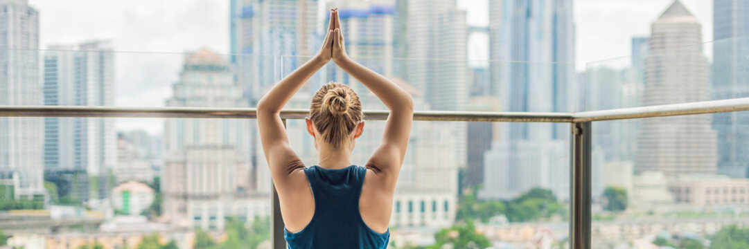 Young woman is practicing yoga in the morning on her balcony with a panoramic view of the city and skyscrapers BANNER, long format