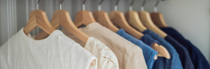 Clothes on hangers in the cabinet gradient from white to dark blue BANNER, long format