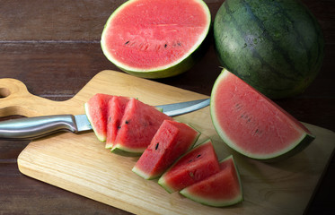 Watermelon slices on chopping board and knife all on wooden table in dim light