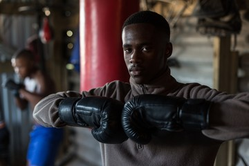Male boxer standing with boxing gloves at fitness studio