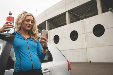 Pregnant woman using mobile phone in parking area