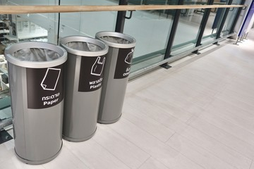 Three grey separate plastic container, which are recycling symbols stamped on paper, plastics, and other materials in front, trash in department store, 3 kinds of recycle bin.