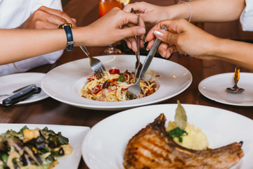 Close up of group of friends hands with a fork having fun eating and having italian dinner together.