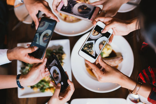 Group of friends going out and taking a photo of Italian food together with mobile phone.