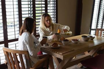 Lesbian couple having coffee in kitchen