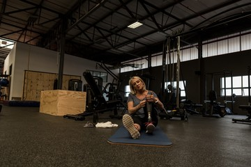 Mature woman with prosthetic leg in the gym