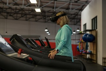 Mature woman using virtual reality headset while exercising on