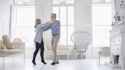 Portrait of older mature couple in love dancing in their white apartment