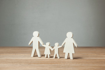 Family symbol, father, mother, daughter and son hold hands on wooden table