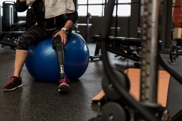 Worried woman sitting on exercise ball in the gym