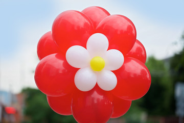 The balloon is bright red in the form of a flower