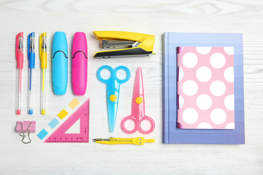 Flat lay composition with different school stationery on wooden background