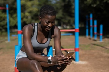 Female athlete using her phone near the bars