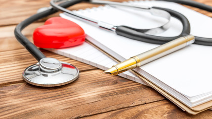 Stethoscope with red heart and notepad on the table.