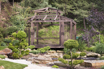 Wooden arbor surrounded by bonsai trees, pines in a Japanese stone garden