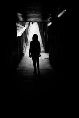 Silhouette of woman alone at the end of a tunnel