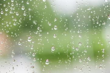 Raindrops on window against defocused blurred background.