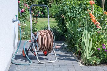 Aufgerollter Gartenschlauch an einer Kaltwasserleitung