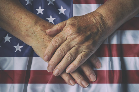 Old woman's hands with American flag