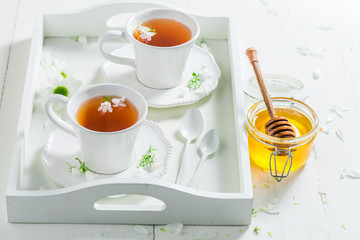Healing two cup of tea with honey on white background