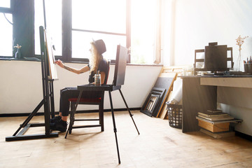 Tattoed amazing blonde curly girl in black hat drawing sketches behind the easel in studio near the sunny window