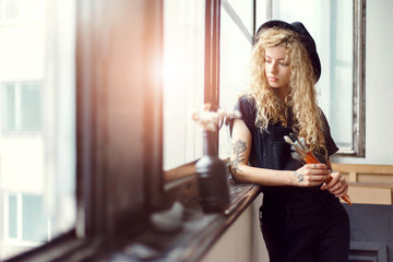 Tattoed long hair female artist in nice black hat looking in window, she holding her brush
