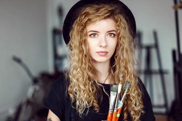 Portrait of blonde long hair female tattoed artist in black hat holding brush