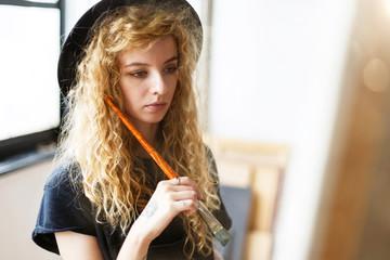 Blonde romantic long hair female artist in black hat holding brush behind the easel in studio near the window