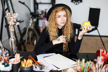 Portrait of romantic blonde long hair curly feemale artist in black hat sitting behind the table with color pencil and green apple