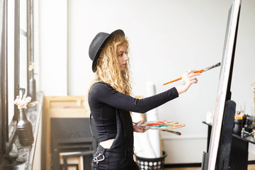 Blonde long hair curly feemale artist in black hat and black clothes drawing with brush and oil behind the easel near the sunny window