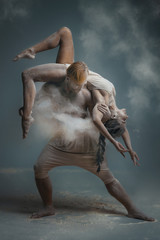 Dancing in flour concept. Girl woman female and muscle fitness guy man male couple in love and in relationship making dance element prefomance in flour / white dust on isolated black / grey background