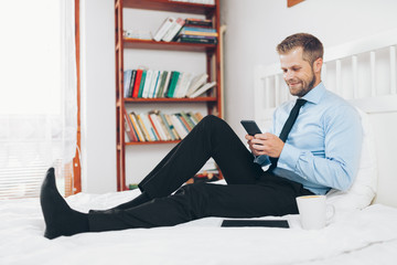 Businessman working from a hotel room with his mobile phone