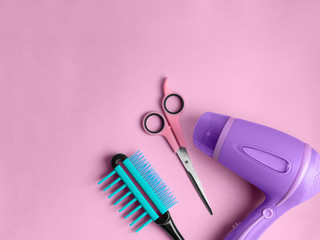 Hairdressing tools Top view Scissors, hair dryer and flat comb are lying on pink background Poster template with empty space