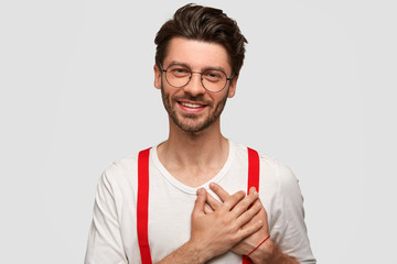 Portrait of happy man keeps both palms on heart, appreciates something with big gratitude, dressed in stylish outfit, has friendly smile, isolated over white background. People, emotions, positivity