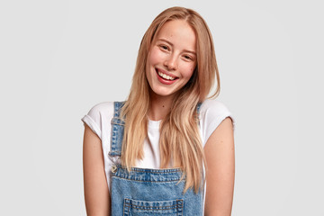 Wall Mural - Beautiful happy Caucasian female with charming smile, dressed in fashionable overalls, has long light hair, expresses positive emotions as sees something pleasant in front, stands against white wall