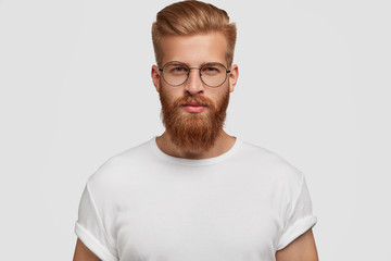 Studio shot of confident attractive man with trendy haairstyle and ginger beard, looks mysteriously at camera, wears white t shirt. Handsome unshaven young male freelancer thinks about future