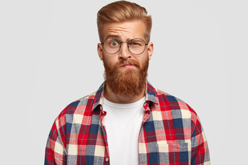 Photo of bewildered puzzled man with thick ginger beard and mustache, raises eyebrows, looks doubtfully at camera, wears fashionable clothes, isolated over white background. Facial expressions