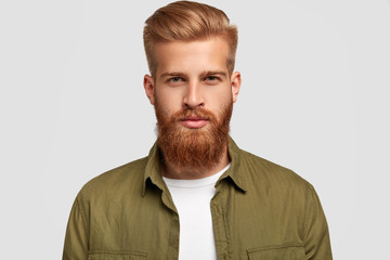 Headshot of attractive bearded man with trendy hairdo, has foxy thick beard and mustache, looks seriously, listens attentively news from interlocutor, isolated over white background. Lifestyle concept