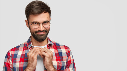 Pleased attractive young bearded man with dark hair, keeps hands together, has intriguing mysterious look, intents prepare surprise to girlfriend, poses over white background with free space